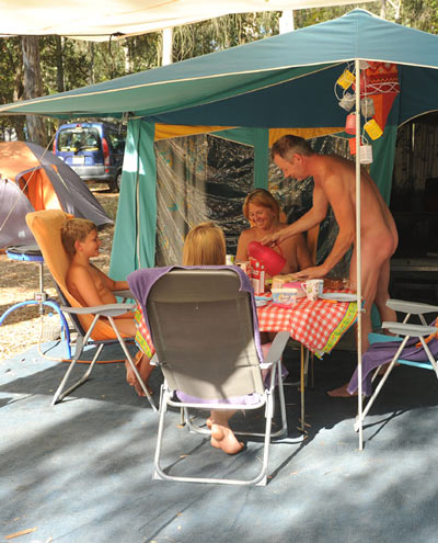 nudist family sitting in a vacation spot near an RV