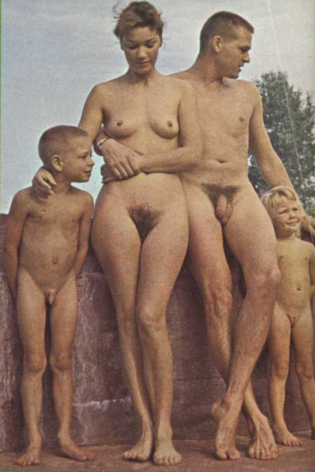 nudist family standing next to a wall
